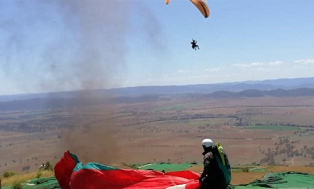 The heart-stopping moment paraglider swept into the air by dirt